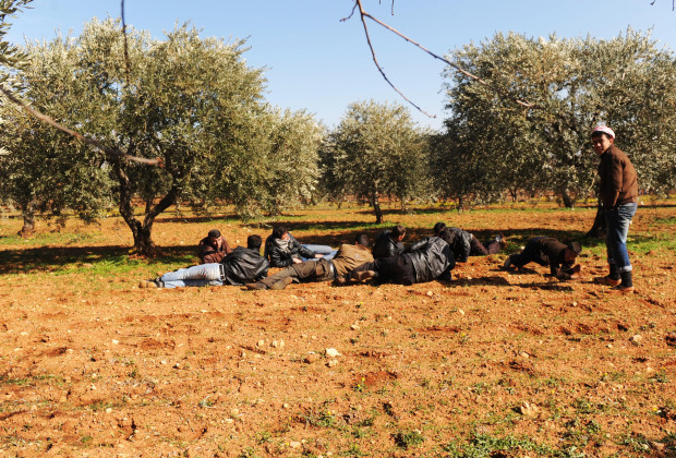 Syrian villagers take cover in an olive grove after an area came under fire by regime forces in Idlib in northwestern Syria on February 22, 2012. Two foreign journalists were killed as Syrian forces pounded the rebel city of Homs, activists said, while calls mounted for a truce to allow in humanitarian aid. AFP PHOTO/BULENT KILIC (Photo credit should read BULENT KILIC/AFP/Getty Images)