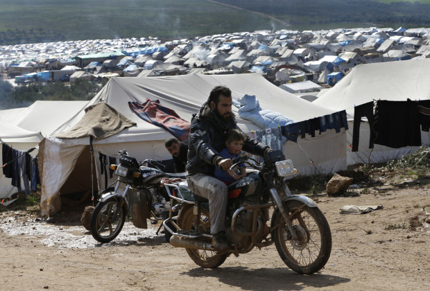 A Syrian refugee, rides his motorcycle with his son at Atmeh refugee camp, in the northern Syrian province of Idlib, Syria, Tuesday Feb. 19, 2013. Camp administrators say that 16,000 people live here in tents pitched amid olive orchards in northwestern Syria. They are supplied by the Turkish Red Crescent, other international agencies and local benefactors but despite being a few dozen meters from the Turkish border they regularly run short of food, tents, and other amenities. (AP Photo/Hussein Malla)