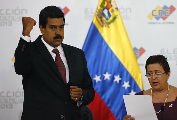 Venezuela's President-elect Nicolas Maduro gestures as Tibisay Lucena, president of the National Electoral Council (CNE), reads a certificate confirming him as winner of Sunday's election, in Caracas, April 15, 2013. The day after Venezuela's election board declared acting President Maduro winner of Sunday's presidential vote by a tight margin, rival candidate Henrique Capriles insisted the opposition's own count showed he was the victor and accused the government of conspiring to hide the truth to remain in power.    REUTERS/Carlos Garcia Rawlins (VENEZUELA - Tags: POLITICS ELECTIONS)