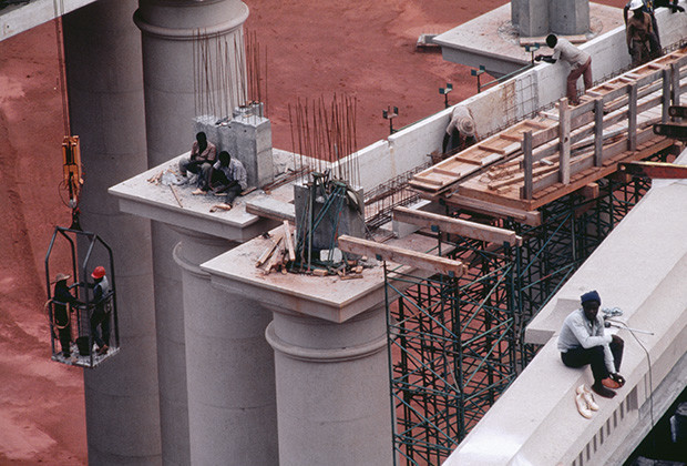 1986-1989, Yamoussoukro, CÙte d'Ivoire --- Workers perch on one of the 120 immense columns measuring 21 meters in height on the construction site of the African Basilica, Notre Dame de la Paix. --- Image by © Sophie Elbaz/Sygma/Corbis