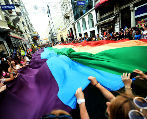 People and activists hold a giant rainbow flag as they shout slogans on Istiklal Street, Istanbul's main shopping corridor, on June 30, 2013, during the fourth Trans Pride Parade as part of the Trans Pride Week 2013, organized by Istanbul's 'Lesbians, Gays, Bisexuals, Transvestites and Transsexuals' (LGBTT) solidarity organization. AFP PHOTO/OZAN KOSE