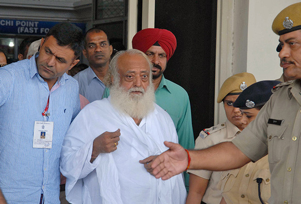 Police escort spiritual leader Asaram Bapu (C) outside an airport after his arrest in Jodhpur, in India's desert state of Rajasthan September 1, 2013. Police arrested Bapu from India's central Madhya Pradesh state late on Saturday night and transited him to neighbouring Rajasthan for further questioning on charges of sexual assault on a minor. REUTERS/Stringer (INDIA - Tags: RELIGION CRIME LAW TPX IMAGES OF THE DAY) - RTX133BU