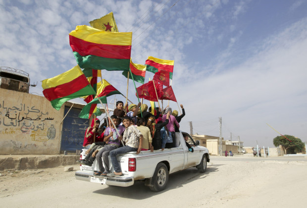 People sit in the back of a truck as they celebrate what they said was the liberation of villages from Islamist rebels near the city of Ras al-Ain in the province of Hasakah, after capturing it from Islamist rebels November 6, 2013. Redur Xelil, spokesman for the armed wing of the Syrian Kurdish Democratic Union Party (PYD), said Kurdish militias had seized the city of Ras al-Ain and all its surrounding villages. Syrian Kurdish fighters have captured more territory from Islamist rebels in northeastern Syria, a Kurdish militant group said on Monday, tightening their grip on an area where they have been setting up autonomous rule.  REUTERS/Stringer (SYRIA - Tags: POLITICS CIVIL UNREST TPX IMAGES OF THE DAY) - RTX152W6