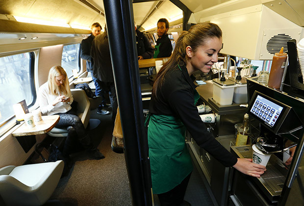An employee of Starbucks prepares a cup of coffee at a new Starbucks store on a train of Swiss rail operator SBB in Zurich November 14, 2013. The world's largest coffee chain Starbucks presented its first double-deck store on a SBB Intercity train travelling between the Swiss cities of St. Gallen and Geneva.  REUTERS/Arnd Wiegmann (SWITZERLAND - Tags: BUSINESS FOOD TRANSPORT TRAVEL) - RTX15DG9