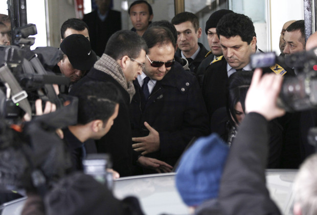 Baris Guler (C in sunglasses), son of Turkey's Interior Minister Muammer Guler, is escorted by plainclothes police officers as he leaves a medical check-up in Istanbul December 16, 2013. Turkish police detained the sons of three cabinet ministers and several well-known businessmen as part of investigations into alleged corruption on Tuesday, state officials said, in a blow to Prime Minister Tayyip Erdogan months ahead of elections. Police carried out dawn raids in the main commercial city Istanbul, detaining at least 18 people including prominent business figures, and searched the headquarters of state-run Halkbank in the capital Ankara, state officials and banking sources said. Picture taken December 16, 2013. REUTERS/Kursat Bayhan/Zaman Daily via Cihan News Agency (TURKEY - Tags: POLITICS BUSINESS CRIME LAW) ATTENTION EDITORS - THIS IMAGE HAS BEEN SUPPLIED BY A THIRD PARTY. IT IS DISTRIBUTED, EXACTLY AS RECEIVED BY REUTERS, AS A SERVICE TO CLIENTS. FOR EDITORIAL USE ONLY. NOT FOR SALE FOR MARKETING OR ADVERTISING CAMPAIGNS. TURKEY OUT. NO COMMERCIAL OR EDITORIAL SALES IN TURKEY - RTX16MAT