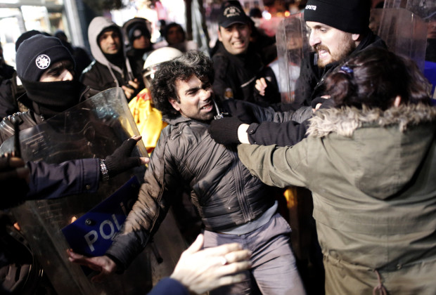 epa03996530 Turkish riot police detain protestors during an anti governmet protest for 13th anniversary of the police operation in prisons against leftist prisoners during their hunger strikes on 2000, in istanbul, Turkey, 19 December 2013.  EPA/SEDAT SUNA