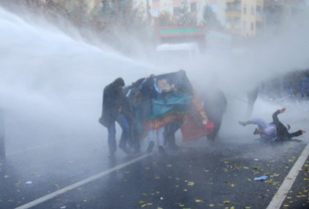 A Kurdish protester falls to the ground as Turkish riot police use water cannons to disperse them during a demonstration in Diyarbakir on December 8, 2013, a day after the funerals of 34 year-old Veysel Isbilir and 32 year-old Mehmet Resit Isbilir in the Yuksekova district in the province of Hakkari. About ten people, including four police officers, were injured in clashes between police and protesters in Diyarbakir where tensions remain high after the death of two Kurdish demonstrators on December 6. AFP PHOTO / MEHMET ENGIN        (Photo credit should read MEHMET ENGIN/AFP/Getty Images)