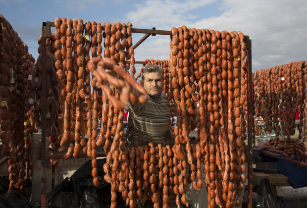 Butcher Serkan Varli tosses camel sausages to a counterpart for grilling. Camel sausage sandwiches are a popular treat at camel wrestling tournaments. Unfortunately loser camels sometimes end up being sold for sausages. Photo by Jodi Hilton/Vocativ