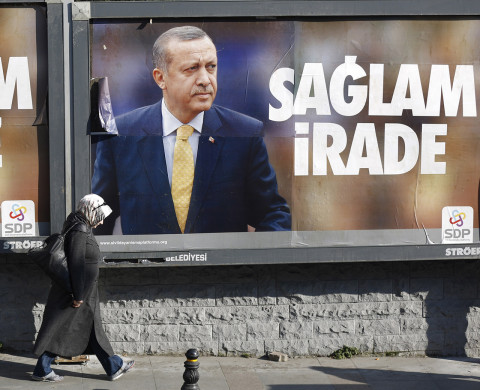 "A woman walks past by billboards with pictures of Turkish Prime Minister Tayyip Erdogan, in Istanbul January 13, 2014. Erdogan vowed on Sunday to forge ahead with judicial reforms which prompted a fist fight in parliament, denying he was trampling on the constitution as the government battles a damaging corruption scandal. The slogan on the pro-Erdogan advertisement posters placed by the Civil Solidarity Platform reads as ""Strong willpower"". REUTERS/Murad Sezer (TURKEY - Tags: POLITICS) - RTX17CH5"