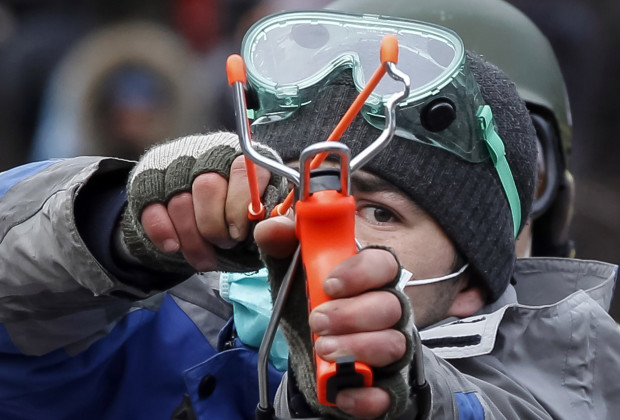 A pro-European integration protester uses a slingshot during clashes with police in Kiev January 20, 2014. Protesters clashed with riot police in the Ukrainian capital on Sunday after tough anti-protest legislation, which the political opposition says paves the way for a police state, was rushed through parliament last week.  REUTERS/Vasily Fedosenko  (UKRAINE - Tags: POLITICS CIVIL UNREST) - RTX17MT0