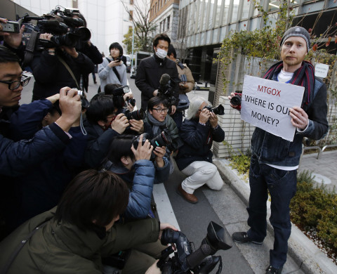 Kolin Burges (R), a self-styled cryptocurrency trader and former software engineer from London, holds a placard to protest against Mt. Gox, as photographers take photos of him in front of the building where the digital marketplace operator was formerly housed in Tokyo February 26, 2014. Japanese authorities are looking into the abrupt closure of Mt. Gox, the top government spokesman said on Wednesday in Tokyo's first official reaction to the turmoil at what was the world's biggest exchange for bitcoin virtual currency.    REUTERS/Toru Hanai (JAPAN - Tags: BUSINESS SCIENCE TECHNOLOGY CIVIL UNREST) - RTR3FQ9B