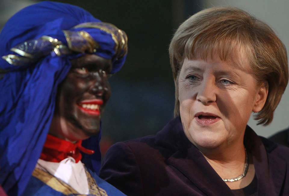 German Chancellor Angela Merkel (R) speaks with a Sternsinger (carol singer) dressed as Balthasar, one of the Three Wise Men, at the Chancellery in Berlin.