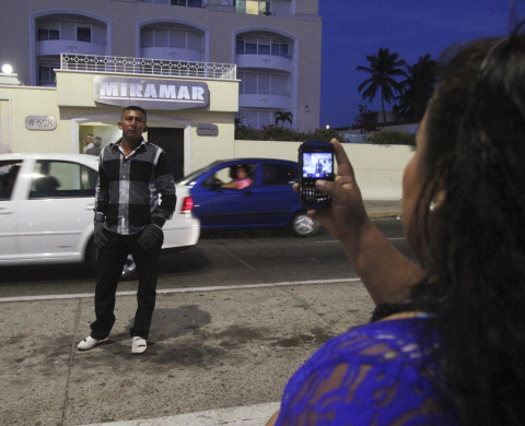 "A woman takes a photograph of a man posing outside the Miramar building where drug kingpin Joaquin ""Shorty"" Guzman was captured earlier in Mazatlan February 22, 2014. Guzman, was captured early on Saturday with help from U.S. agencies in a major victory for the government in a long, brutal drugs war. He has long run Mexico's infamous Sinaloa Cartel and over the past decade emerged as one of the world's most powerful organized crime bosses.  REUTERS/Stringer (MEXICO - Tags: CRIME LAW CIVIL UNREST DRUGS SOCIETY) - RTX19C9O"