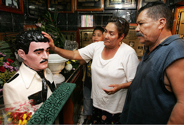 A Mexican couple visits the Malverde chapel in Culiacan in Mexico's state of Sinaloa September 17, 2005. In Sinaloa, Santo Malverde is said to be the patron saint of drug smugglers. Jesus Malverde who robbed the rich to give to the poor was a real-life Robin Hood figure in the late 1800s. A chapel stands at the railroad crossing, near the site where Malverde was hanged in 1910. Malverde has also become the protector of migrant workers, prostitutes and one-legged men. Believers pin testimonies to the walls of the chapel, adorned with flowers and candles around an encased plastic head of the saint. For decades Sinoloa has been Mexico's breadbasket. Its fertile fields have produced huge crops of soybean and sesame seeds, and vast amounts of marijuana and heroin destined for U.S. markets.