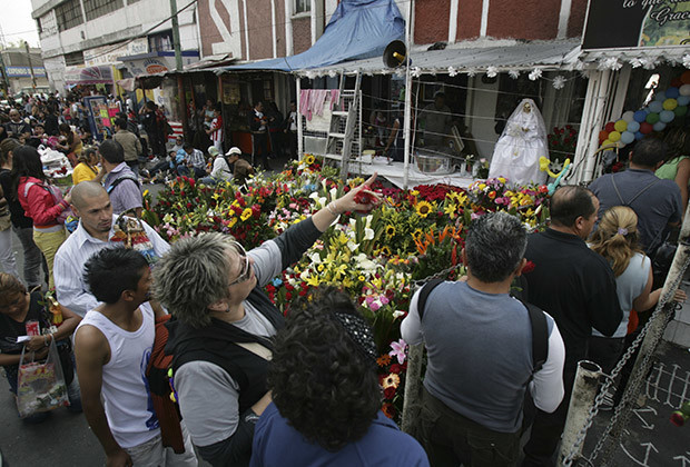 "MEXICO CITY, MEXICO - NOVEMBER 01: Hundreds of worshipers reach to the holy death of Tepito shrine to worship the ""white girl"" on the day of the dead saints as part of the celebrations of the Day of the Dead on November 01, 2012 in Mexico City, Mexico."
