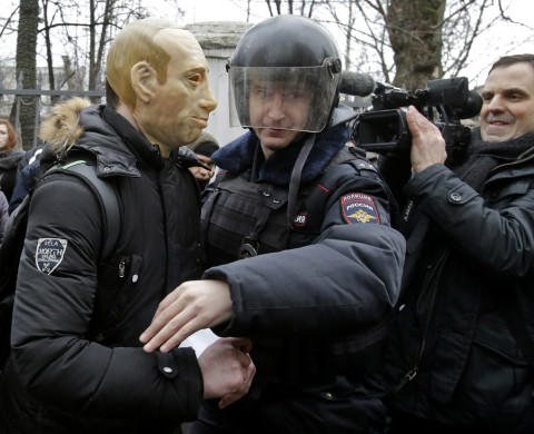 Police detain a protester outside a courthouse in Moscow February 24, 2014. Russian police detained dozens of protesters on Monday outside a Moscow courthouse where a judge was expected to sentence eight defendants convicted of attacking police at a 2012 demonstration against President Vladimir Putin. REUTERS/Tatyana Makeyeva (RUSSIA - Tags: CIVIL UNREST CRIME LAW POLITICS) - RTX19E8D