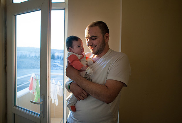 Gaziantep, Turkey 2014 Bilal  sits for a portrait with his Turkey born baby Selene.