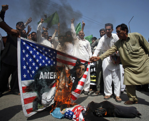 Supporters of the Pakistan Muslim League (Like-Minded) burn an effigy and a U.S. flag with a portrait of U.S. President Barack Obama displayed on it, during a demonstration in Peshawar September 27, 2012. About 25 protesters gathered on Thursday to protest against an anti-Islam film made in the U.S. that insults Prophet Mohammad.  REUTERS/Fayaz Aziz     (PAKISTAN - Tags: POLITICS CIVIL UNREST) - RTR38HH9