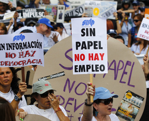 "A woman holds up a sign reading ""No paper, no jobs"", during a protest by newspaper workers and opposition parties to demand from the government U.S. dollars at a prime rate to buy paper for their publications, in Caracas February 11, 2014. Newspaper owners claim they are close to running out of their stock of paper due to the lack of dollars to import it, local media said.  REUTERS/Carlos Garcia Rawlins (VENEZUELA - Tags: POLITICS CIVIL UNREST MEDIA BUSINESS EMPLOYMENT) - RTX18M88"