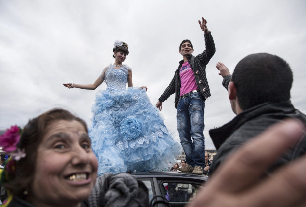 """A Roma couple dances on the roof of a car in order to publicly announce their engagement in the Bulgarian city of Stara Zagora. Every year members of the widely dispersed Kalaidzhi clan have a meeting, called the """"Gypsy Bride Market"""" in order to arrange matches and negotiate bride prices."""