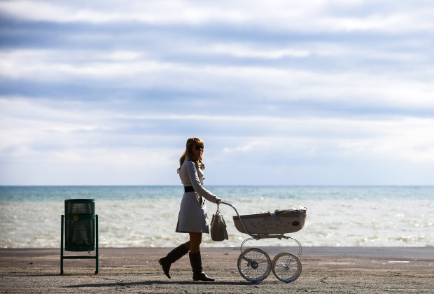 A woman pushes a pram along the embankment in the Black Sea resort town of Alushta March 11, 2014. Ukraine's Crimean peninsular evokes in many Russians and citizens of the former Soviet Union memories of summer holidays in the resorts and sanatoriums along its subtropical Black Sea coast. Crimea is also the place from where Christianity spread throughout what was then called Kievan Rus', a federation of Slavic tribes that later became Russia.  REUTERS/Thomas Peter (UKRAINE - Tags: POLITICS SOCIETY TRAVEL TPX IMAGES OF THE DAY) - RTR3GNN3