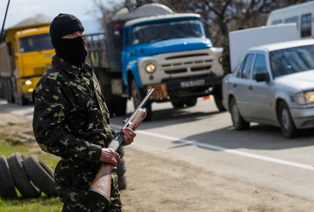 An armed member of a local self-defence unit watches traffic at a checkpoint on the highway between Simferopol and Sevastopol in the Crimea peninsular March 13, 2014. Ukraine's parliament appealed on Thursday to the United Nations to discuss the occupation by Russian forces of its Crimea peninsula and said it reserved the right to ask individual countries for help in resolving the issue.   REUTERS/Thomas Peter (UKRAINE  - Tags: POLITICS MILITARY) - RTR3GWVS