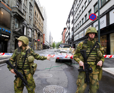 Soldiers guard near a cordoned area in Akersgata, Oslo, July 23, 2011. A suspected far-right gunman in police uniform killed at least 84 people in a ferocious attack on a youth summer camp of Norway's ruling Labour party, hours after a bomb killed seven in Oslo. Witnesses said the gunman, identified by police as a 32-year-old Norwegian, moved across the small, wooded island of Utoeya in a lake northwest of Oslo on Friday, firing at young people who scattered in panic or tried to swim to safety. EUTERS/Berit Roald/Scanpix (NORWAY - Tags: CRIME LAW MILITARY) FOR EDITORIAL USE ONLY. NOT FOR SALE FOR MARKETING OR ADVERTISING CAMPAIGNS. THIS IMAGE HAS BEEN SUPPLIED BY A THIRD PARTY. IT IS DISTRIBUTED, EXACTLY AS RECEIVED BY REUTERS, AS A SERVICE TO CLIENTS. NORWAY OUT. NO COMMERCIAL OR EDITORIAL SALES INNORWAY - RTR2P6S8