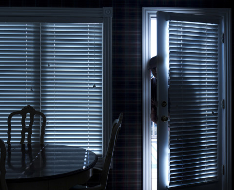 Burglar Breaking In To Home At Night Through Back Door