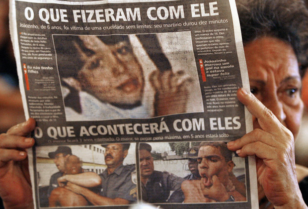 "Rio de Janeiro, BRAZIL: A woman holds a newspaper showing the picture of Joao Helio Fernandes and his murderers and the headlines ""what they have done with him"" and ""what will happen with them"", during a 7 day-mass for Joao Helio Fernandes(6) at the Candelaria church in Rio de Janeiro, 14 February 2007. Joao Helio's tragedy ocurred on February 7th when two assailants stopped a car in which Joao was traveling, threatened his mother and sister with a weapon and ordered them out.  As Joao's mother tried to undo the seatbelt on the child, the thieves drove off, dragging the trapped boy outside the car for seven kilometers (four miles) on a 15-minute joyride across three northern Rio neighborhoods, despite the screams of horrified witnesses. Thousand of citizens protested on Wednesday against violence in Rio de Janeiro.   AFP PHOTO/VANDERLEI ALMEIDA (Photo credit should read VANDERLEI ALMEIDA/AFP/Getty Images)"