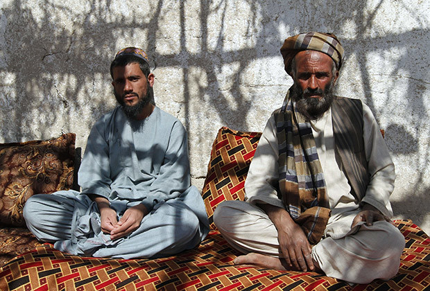 Sher Mohammad (L), one of the 65 prisoners released from Bagram prison, sits with his uncle at his home at Zhari district, Kandahar province February 23, 2014. President Hamid Karzai's decision in February 2014 to release the disputed 65 prisoners is a sign of his growing eagerness to assert his independence from his Western backers.