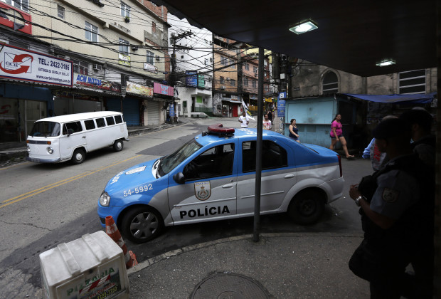 "Police officers (R) from the Police Peacekeeping Unit (UPP), a security programme in which the EBX Group owned by Brazilian billionaire Eike Batista had invested, stand near their vehicle as they patrol the Rocinha slum in Rio de Janeiro October 17, 2013. Investors who bet on Batista have lost billions over the past year as the Brazilian's ephemeral business empire, built on a series of mining, energy and shipping companies, imploded. However, they haven't been the only losers – the onetime Amazon gold trader and former speedboat racer's hometown of Rio de Janeiro has also been shaken by his rapid decline. Batista had struck a multi-year partnership with the Rio state government to contribute 20 million reais ($9.19 million) annually from 2010, to the ongoing effort to ""pacify"" the slums, but he pulled out of the partnership in August. Picture taken October 17. To match Insight BRAZIL-BATISTA/RIO         REUTERS/Ricardo Moraes (BRAZIL - Tags: CRIME LAW BUSINESS TRANSPORT SOCIETY POVERTY) - RTX14HOZ"