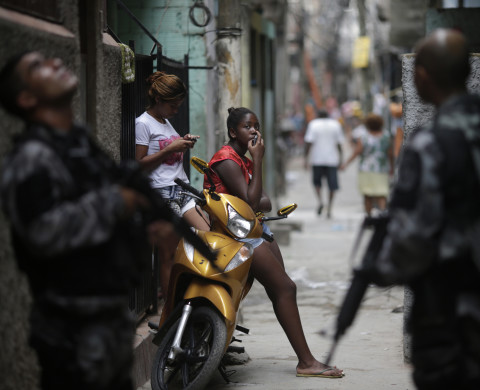Girls rest along an alley as police officers patrol during an operation at the Mare slums complex in Rio de Janeiro March 25, 2014. Brazil will deploy federal troops to Rio de Janeiro to help quell a surge in violent crime following attacks by drug traffickers on police posts in three slums on the north side of the city, government officials said on Friday. Less than three months before Rio welcomes tens of thousands of foreign soccer fans for the World Cup, the attacks cast new doubts on government efforts to expel gangs from slums using a strong police presence. The city will host the Olympics in 2016. REUTERS/Ricardo Moraes (BRAZIL - Tags: CRIME LAW) - RTR3IKFQ