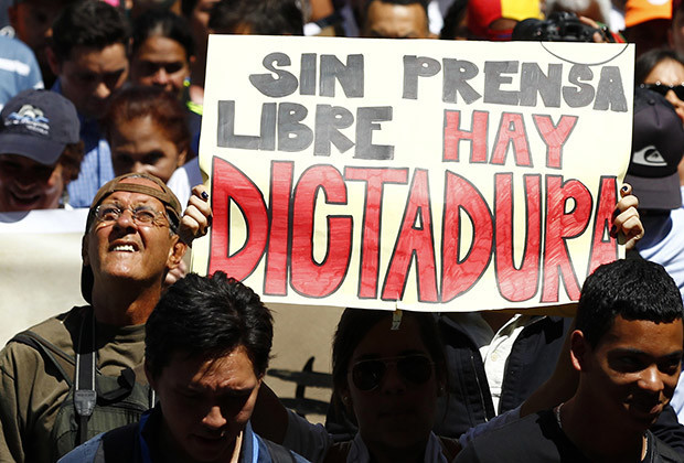 "A woman holds up a sign reading ""'Without free press, there is a dictatorship"", during a protest by newspaper workers and opposition parties to demand from the government U.S. dollars at a prime rate to buy paper for their publications, in Caracas February 11, 2014. Newspaper owners claim they are close to running out of their stock of paper due to the lack of dollars to import it, local media said.  REUTERS/Carlos Garcia Rawlins (VENEZUELA - Tags: POLITICS CIVIL UNREST MEDIA BUSINESS) - RTX18M7N"