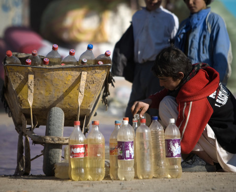 An Afghan vendor fills a bottle with oil in the Islamghale area near Iran and Afghanistan border December 17, 2009. REUTERS/Morteza Nikoubazl (AFGHANISTAN - Tags: SOCIETY ENERGY) - RTXRXVV