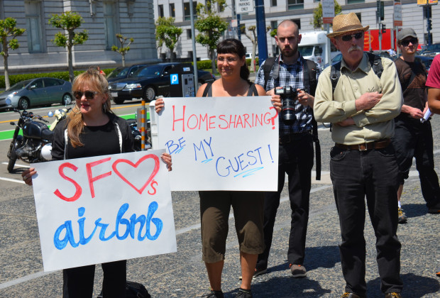 Two women hold 'SF loves airbnb' and 'Homesharing? be my guest!' signs to support home sharing at the rally. -- People held a rally at City Hall to support home sharing, the renting out of extra bedrooms in homes, and opposed a possible ballot initiative aimed at heavily regulating the practice, stronger than proposed local Board of Supervisors legislation.