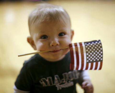 Dylan Curry, 11 months old, carries a U.S. flag in his mouth as he waits for his U.S. Army soldier father to return from Iraq before a ceremony at Fort Carson in Colorado Springs, Colorado February 12, 2009. About 280 soldiers from the 3rd Brigade Combat Team, 4th Infantry Division returned following their 15-month deployment to Iraq.  REUTERS/Rick Wilking (UNITED STATES) - RTXBKAT