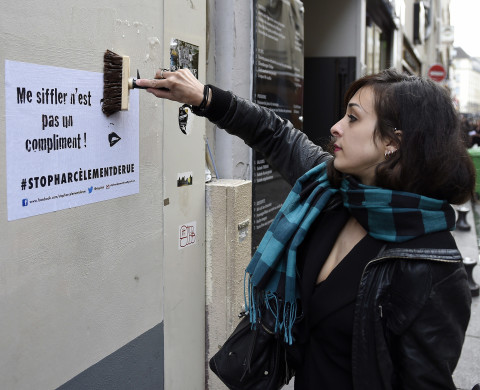 "A woman pastes a flyer with text reading ""Whistling at me is not a compliment"" on a wall as she takes part in a protest against sexual and verbal harassment, on April 25, 2014, in Paris. A group of protesters, including both men and women, gathered in Paris today to denounce sexual and verbal harassment which occurs everyday in the streets."