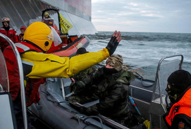 According to Greenpeace, a man identified as a Russian coast guard officer points a knife an activist. (Reuters/Denis Sinyakov)