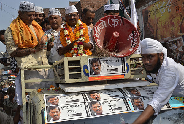 Arvind Kejriwal (wearing garlands), the leader of the anti-corruption Aam Aadmi Party (AAP), stands atop a vehicle after ink was hurled at him and other party workers during a public rally ahead of the general elections in Varanasi, in the northern Indian state of Uttar Pradesh, March 25, 2014. The world's largest democracy goes to the ballot box next month.