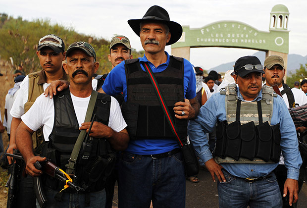 Jose Manuel Mireles (C), head of Michoacan state's community police, stands with vigilantes in Churumuco in Michoacan state December 29, 2013. Mireles and four other people were injured when the plane they were travelling in suffered an accident on January 4, 2014, with one of the injured dying after arriving at the hospital. Mireles suffered a mild head injury and a dislocated jaw, but he is stable and conscious, according to a communique from the prosecutor's office. Michoacan has been rocked by repeated explosions of civil unrest in 2013 and vigilante groups have sprung up in the region which complain that state and federal police are not protecting them from the gangs. Picture taken December 29, 2013.
