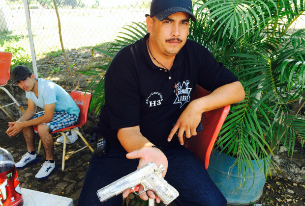 "BUENA VISTA, MEXICO--January 17, 2013: Luis Antonio Torres Gonzalez, known as ""El Americano"", a leader of the militia movement, shows off a pistol he says was confiscated from the Knights Templar drug gang."