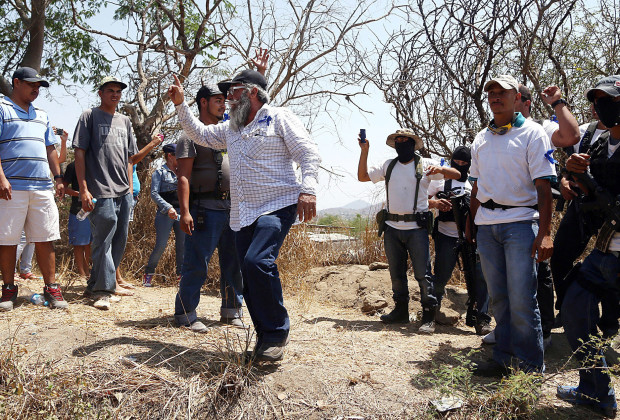 One of the leaders of a self-defence group, Estanislao Beltran aka Papa Pitufo (C), speaks at the entrance of Arteaga, in the state of Michoacan, Mexico, on April 22, 2014. Michoacan, where much of the population lives in poverty, has become the most pressing security issue facing Mexico President Enrique Pena Nieto, who inherited a bloody war on drugs.