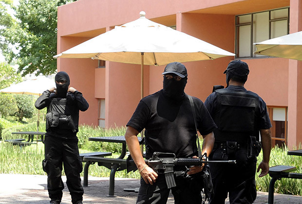 Policemen guard the entrance to the Tecnologico de Monterrey University, in Atizapan, State of Mexico, Mexico, on Aug. 8, 2011. An artifact exploded inside the university's teachers lounge leaving two teachers injured.
