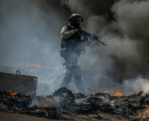 A Ukrainian security force officer is deployed at a checkpoint set on fire and left by pro-Russian separatists near Slaviansk April 24, 2014. Ukrainian forces clashed with pro-Russian militants as they closed in on the separatist-held city of Slaviansk on Thursday, seizing rebel checkpoints and setting up roadblocks as helicopters circled overhead. Reuters journalists saw a Ukrainian detachment with five armoured personnel carriers take over the checkpoint on a road north of the city in late morning after it was abandoned by separatists who set tyres alight to cover their retreat.  REUTERS/Gleb Garanich (UKRAINE - Tags: POLITICS CIVIL UNREST MILITARY) - RTR3MGE7
