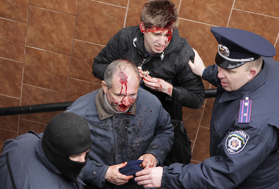 Interior Ministry members stand near men, who were injured in clashes between pro-Russian and pro-Ukrainian supporters during their rallies, in Kharkiv, April 13, 2014.