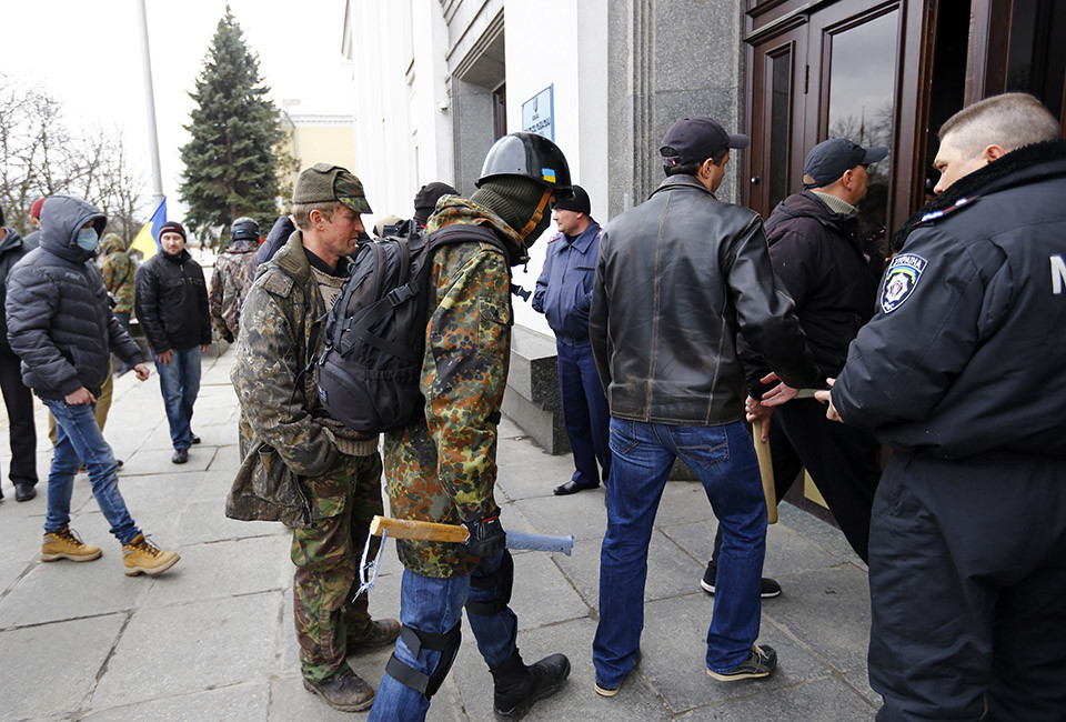 Pro-Ukrainian supporters walk into the regional administration headquarters in Luhansk, in eastern Ukraine April 14, 2014. Ukraine's president on Monday threatened military action after pro-Russian separatists occupying government buildings in the east ignored an ultimatum to leave and another group of rebels attacked a police headquarters in the troubled region.