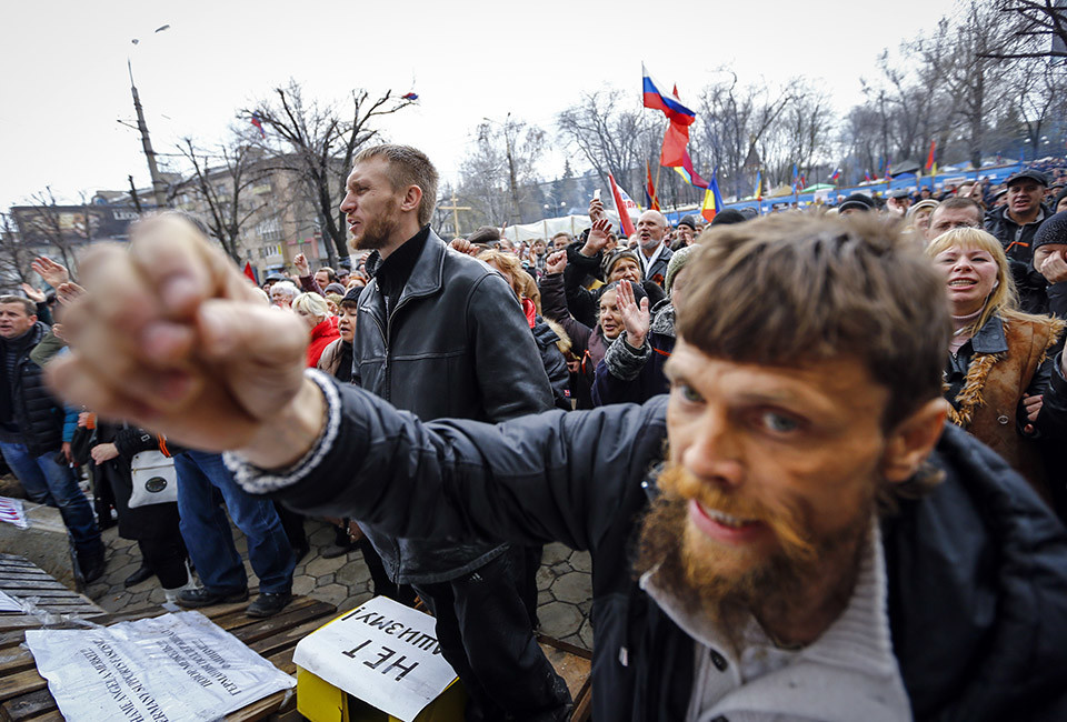 Pro-Russian protesters attend a rally in front of the seized office of the SBU state security service in Luhansk, eastern Ukraine April 14, 2014. Ukraine's president on Monday threatened military action after pro-Russian separatists occupying government buildings in the east ignored an ultimatum to leave and another group of rebels attacked a police headquarters in the troubled region.