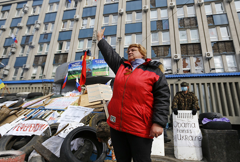 """A pro-Russian protester gestures at a barricade in front of the seized office of the SBU state security service in Luhansk, in eastern Ukraine April 14, 2014. Towns in eastern Ukraine on Monday braced for military action from government forces after Kiev gave pro-Russian separatists a 9 a.m. (0600 GMT) deadline to disarm and end their occupation of state buildings or face a major """"anti-terrorist"""" operation."""