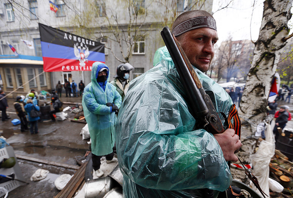 A pro-Russian armed man stands guard at a barricade near the police headquarters in Slaviansk April 13, 2014. Ukrainian security forces launched an operation on Sunday to clear pro-Russian separatists from the headquarters, with Kiev reporting dead on both sides as it combats what it calls an act of aggression by Moscow.