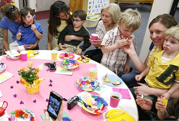 Students and parents in the Lookout Mountain Preschool a variety of snacks at a school party for Mother's Day in Golden, Colorado .